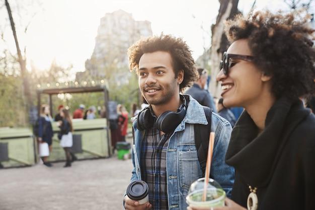 Ritratto di vista laterale dell'affascinante ragazzo afro-americano con taglio di capelli afro che osserva da parte mentre cammina con la sua ragazza nel parco, beve caffè e si gode una serata calda