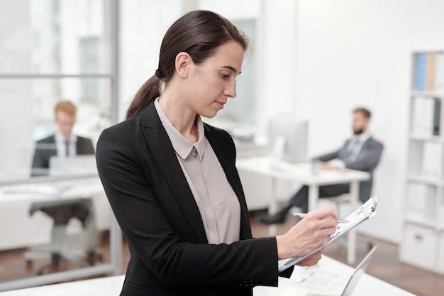 Ritratto di vista laterale della giovane donna di affari che scrive negli appunti mentre levandosi in piedi in ufficio, lo spazio della copia