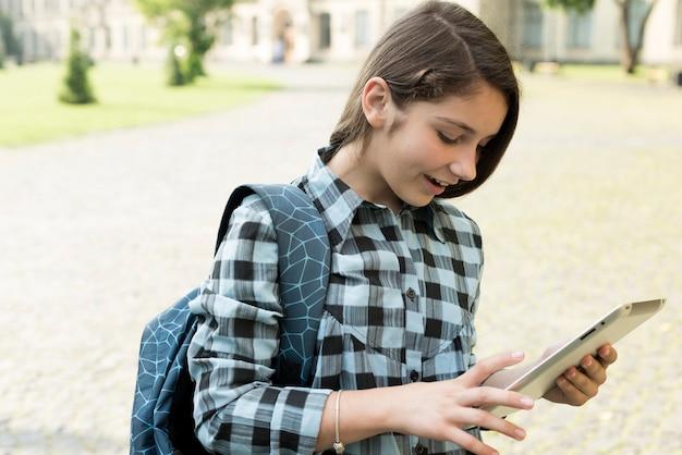 Ritratto di vista laterale della ragazza del liceo facendo uso della compressa