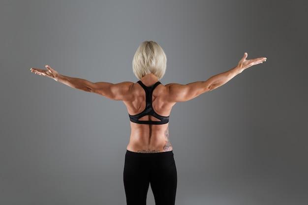 Ritratto di vista posteriore di una sportiva adulta muscolosa
