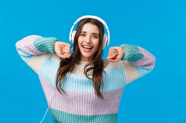 Ritratto di vita spensierata gioiosa ragazza a casa da sola, godendo della libertà e della musica fantastica