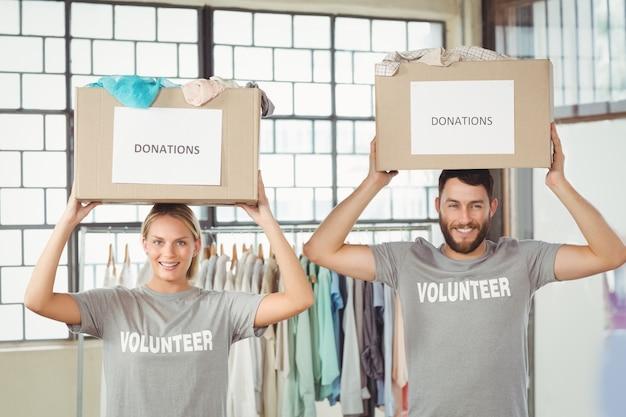 Ritratto di volontari che trasportano scatole di donazione sulla testa