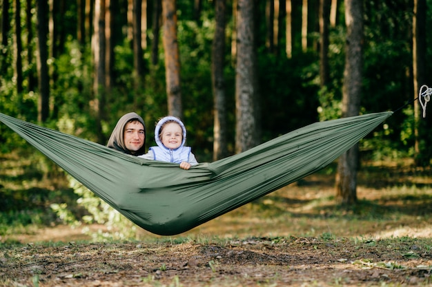 Ritratto divertente del padre con sua figlia sorridente che guarda dall'amaca nella foresta di estate.