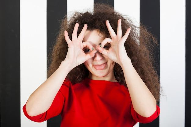Ritratto divertente della ragazza del brunette su priorità bassa a strisce