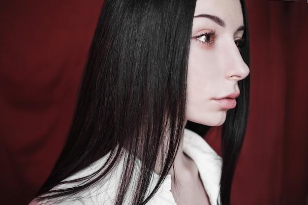 Ritratto emotivo della ragazza bruna con i capelli neri dritti lunghi con un trucco naturale su uno sfondo rosso. donna in camicia sbottonata bianca