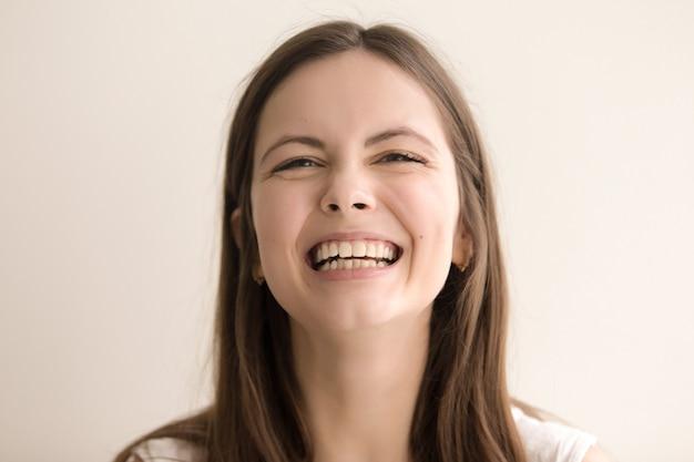 Ritratto emotivo di colpo in testa di giovane donna di risata