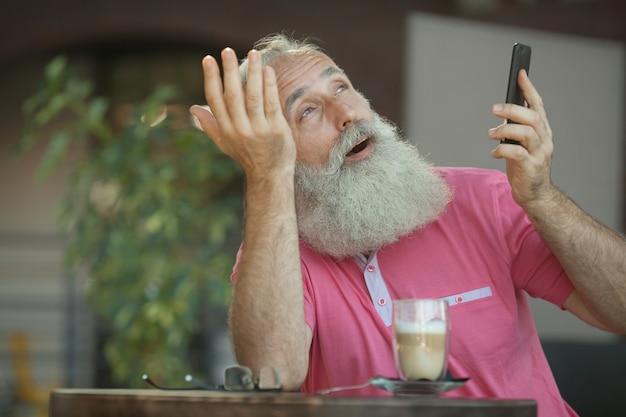 Ritratto emotivo di un uomo allegro ed elegante di affari maturi con la testa calva, con un sorriso che parla sullo smartphone con un amico. uomo anziano barbuto