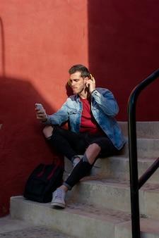 Ritratto esterno del giovane moderno con smart phone seduto in strada.
