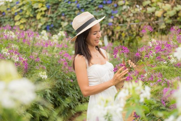 Ritratto esterno di una bella donna di mezza età dell'asia. ragazza attraente in un campo con i fiori