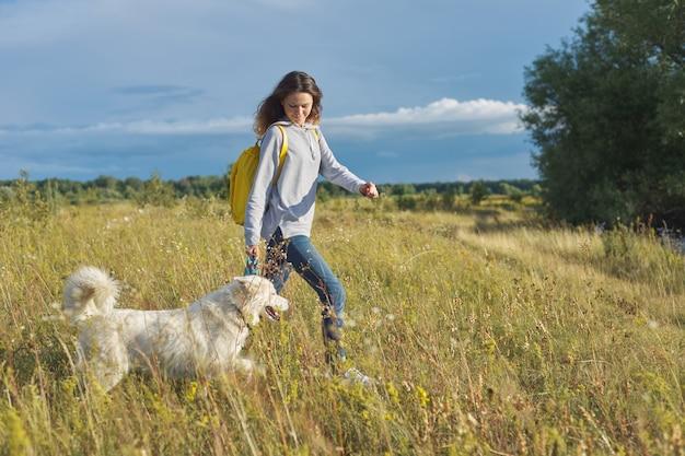 Ritratto esterno dinamico della ragazza corrente con il cane