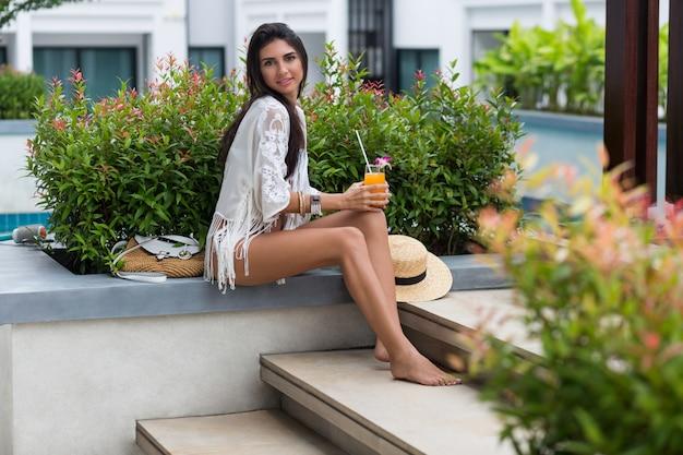 Ritratto estivo all'aperto di donna felice con un corpo abbronzato incredibile, ritardi sottili, bere succo. uno stile di vita sano.