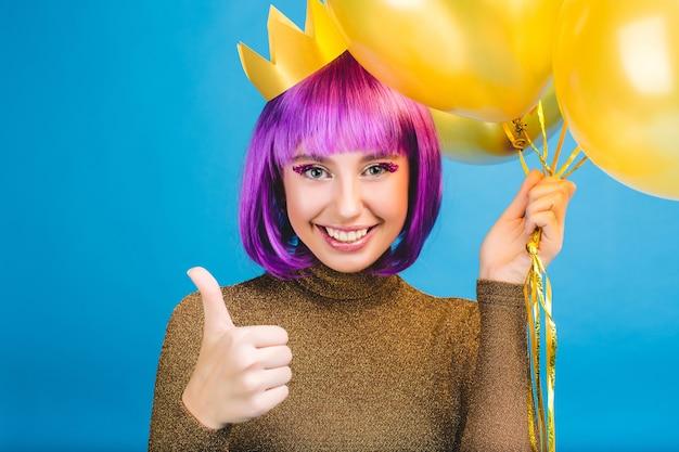 Ritratto felice che celebra momenti di gioiosa giovane donna con palloncini dorati sorridente. abito di lusso, capelli viola tagliati, corona da principessa, umore allegro.