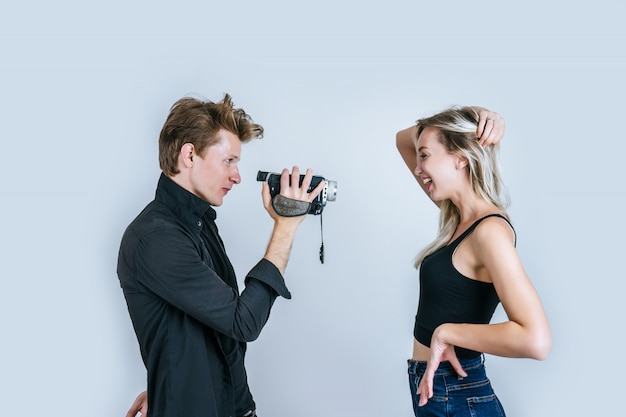 Ritratto felice delle coppie che tengono videocamera e registrano il video della clip