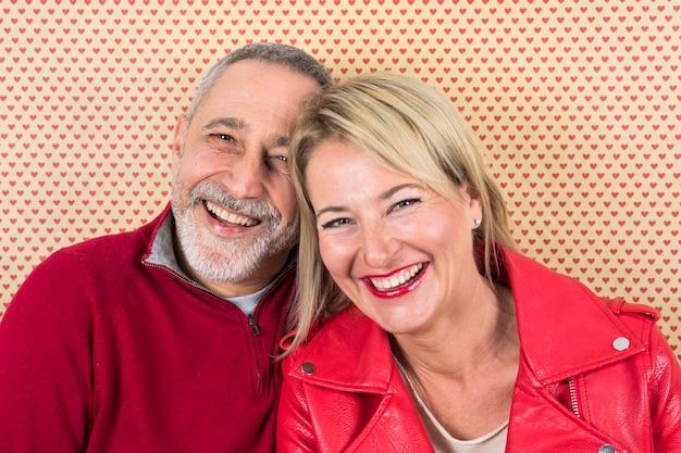 Ritratto felice delle coppie senior contro la carta da parati di forma del cuore