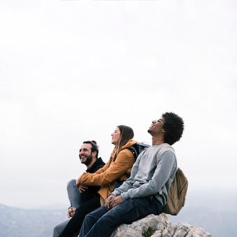 Ritratto felice di giovani amici che si siedono sul picco di montagna