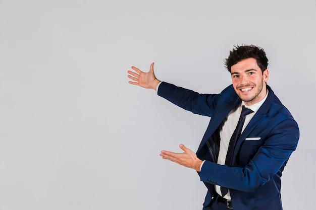 Ritratto felice di un giovane uomo d'affari che dà presentazione contro fondo grigio