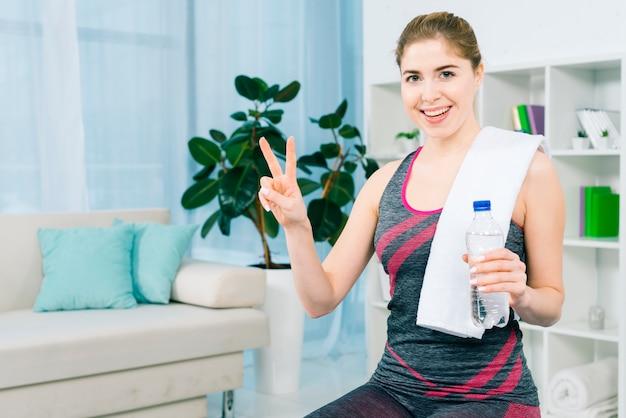 Ritratto felice di una giovane donna esile che tiene la bottiglia di acqua a disposizione che mostra il segno di vittoria