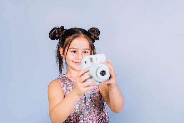 Ritratto felice di una ragazza che esamina macchina fotografica istantanea contro il contesto blu