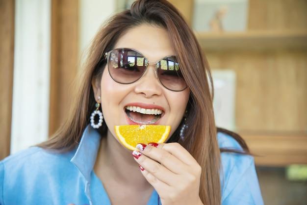 Ritratto felice giovane signora asiatica mangiare arancione