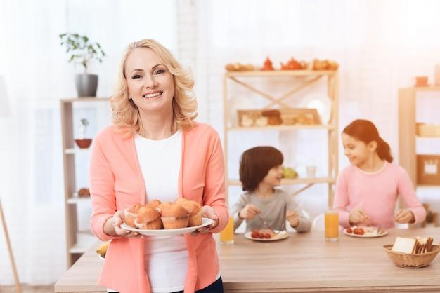 Ritratto felice nonna tenendo il piatto con muffin