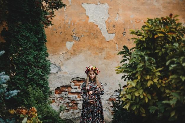 Ritratto femminile affascinante donna incinta in abito di fiori pone