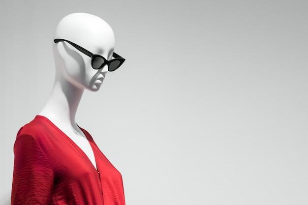 Ritratto femminile del manichino in occhiali da sole e vestito rosso. tema di vendita e pubblicità. copyspace per il testo