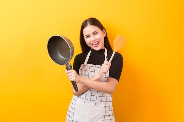 Ritratto femminile felice del cuoco su giallo