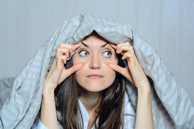 Ritratto frontale del primo piano di una donna che la tiene occhi con le sue mani, che soffrono di insonnia. paura, incubi, fa capolino, vederti, guardare
