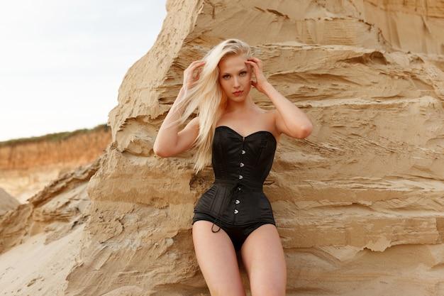 Ritratto frontale di una giovane donna con i capelli biondi e il trucco, vestita di una tuta sexy nera, vicino al muro di sabbia nel deserto.