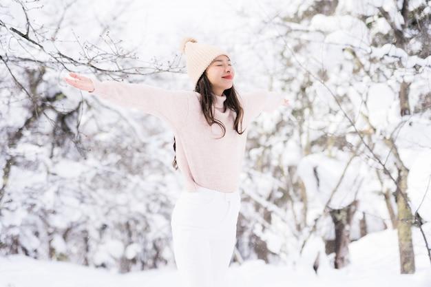 Ritratto giovane bella donna asiatica sorriso felice viaggio e godere con la stagione invernale della neve
