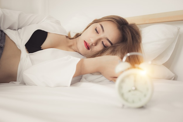 Ritratto giovane bella donna sul letto nella bella camera da letto