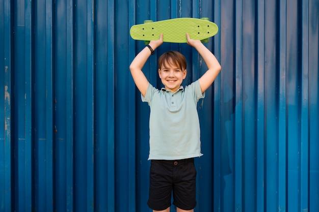 Ritratto giovane ragazzo sorridente cool in polo blu in posa con penny board nelle mani