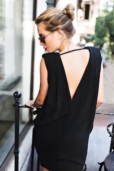 Ritratto graziosa modella in abito nero con schiena nuda sulla terrazza. sta guardando in basso.
