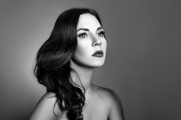 Ritratto in bianco e nero di una donna con il primo piano perfetto della pelle pulita.