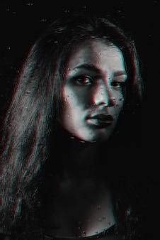 Ritratto in bianco e nero di una ragazza dietro un vetro con gocce di pioggia