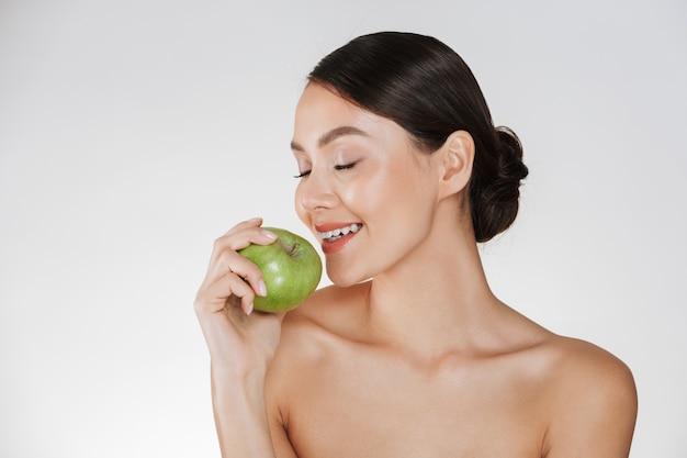 Ritratto in buona salute di giovane donna con pelle fresca molle che gode della mela succosa verde, isolata sopra bianco