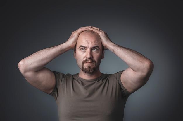 Ritratto in studio di un uomo con le mani sulla sua testa