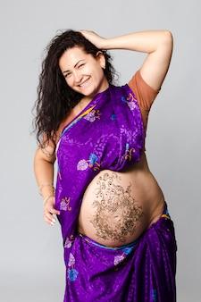 Ritratto in studio di una donna incinta felice in sari indiano, una pancia incinta dipinta con l'henné
