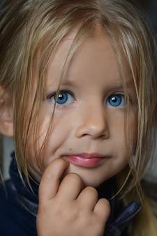 Ritratto in studio di una piccola ragazza bianca seria con i capelli bianchi e gli occhi azzurri