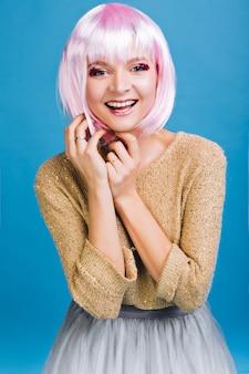 Ritratto incredibile giovane donna con taglio di capelli rosa. trucco luminoso con orpelli rosa, gonna in tulle, espressione di vere emozioni positive, momento magico, festa, celebrazione.