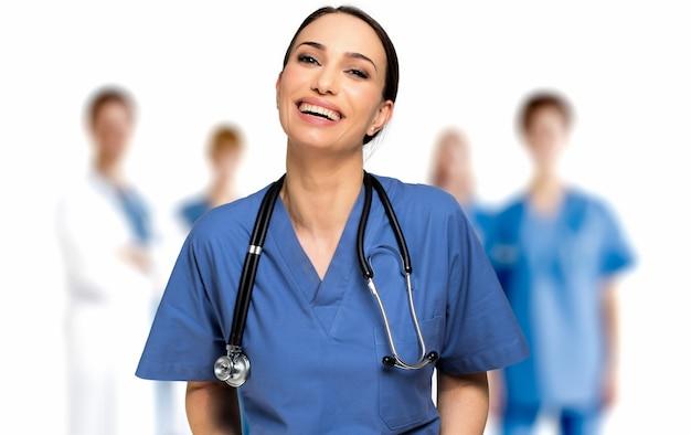 Ritratto infermiera sorridente contro un gruppo di medici