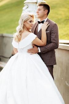 Ritratto integrale del corpo di giovane sposa e sposo che corrono sull'erba verde del campo da golf. coppie felici di nozze che camminano attraverso il campo da golf, spazio della copia
