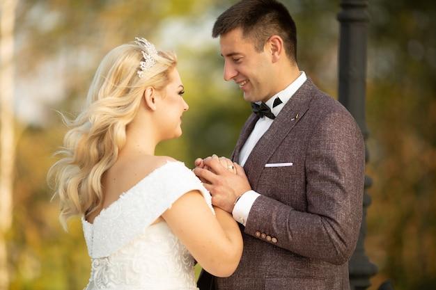Ritratto integrale del corpo di giovane sposa e sposo che corrono sull'erba verde del campo da golf