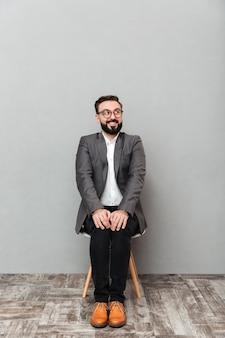 Ritratto integrale del giovane in rivestimento che si siede sulla sedia che mette le mani sulle ginocchia, isolato sopra grey