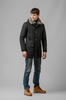 Ritratto integrale dell'uomo bello in cappotto caldo che posa nello studio