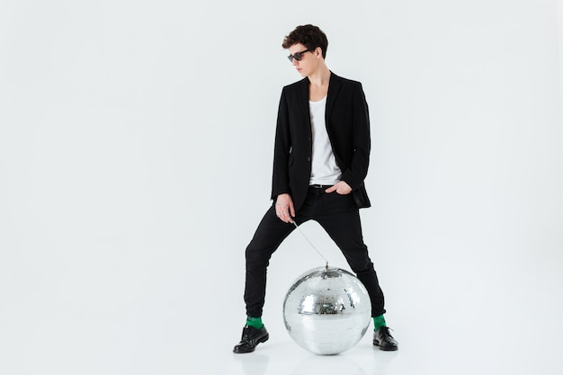 Ritratto integrale dell'uomo in vestito con la palla della discoteca