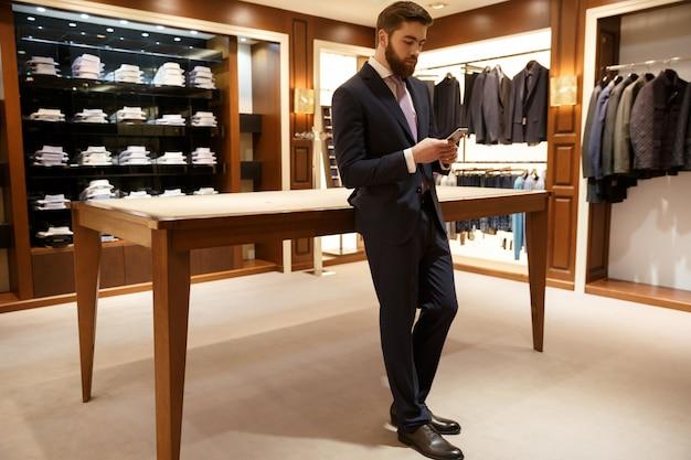 Ritratto integrale dell'uomo in vestito facendo uso dello smartphone