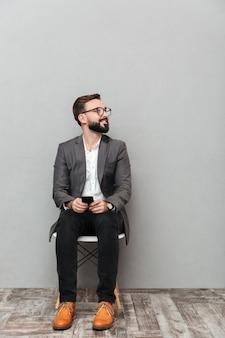 Ritratto integrale dell'uomo rilassato nella seduta casuale sulla sedia in ufficio che guarda da parte con lo smartphone in mani, isolato sopra grey