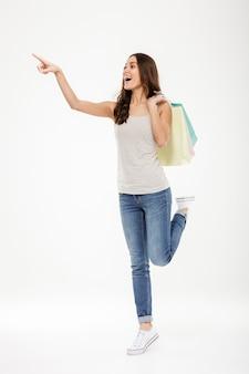 Ritratto integrale della donna d'avanguardia che indica dito lontano e che tiene molti sacchetti della spesa, isolato sopra la parete bianca