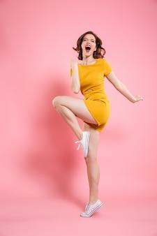 Ritratto integrale della giovane donna graziosa in vestito giallo elegante che mostra gesto del vincitore,